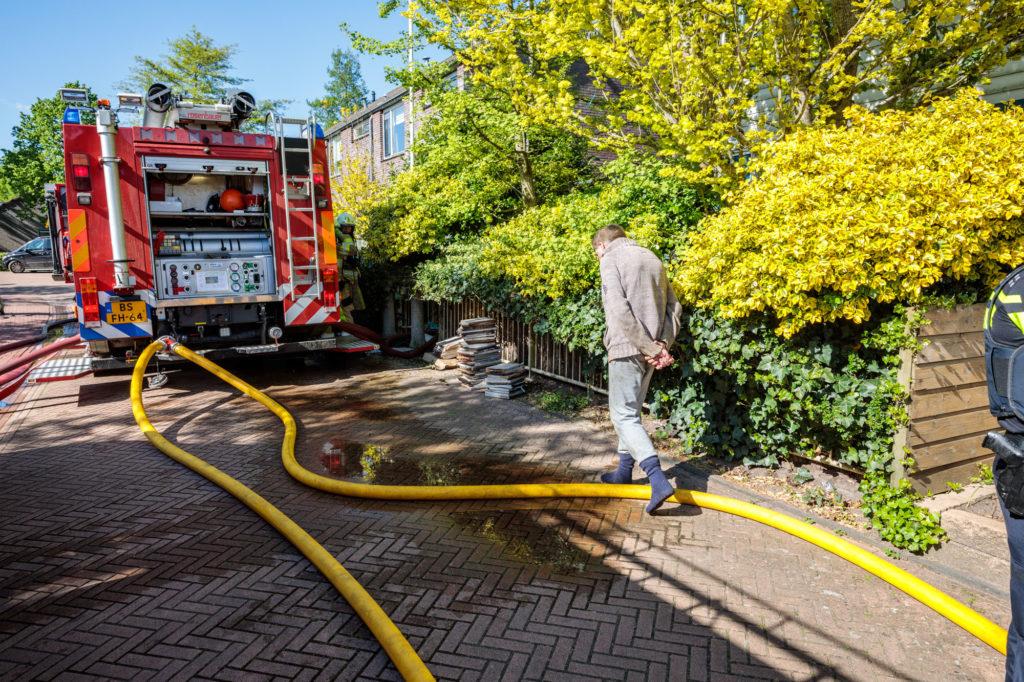 De bewoner hield de werkzaamheden van de brandweer verslagen in de gaten.